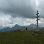 Auf dem Kreuzjoch informiert eine Panoramatafel, im Norden der Ifinger, im Hintergrund der Hirzer